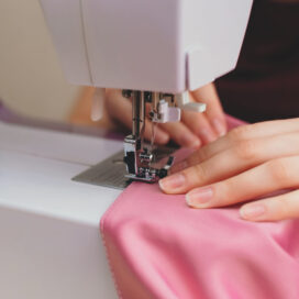 Happy attractive young woman seamstress sitting and sews on sewing machine on light background. Concept of sewing, handmade goods. Advertising of studio.